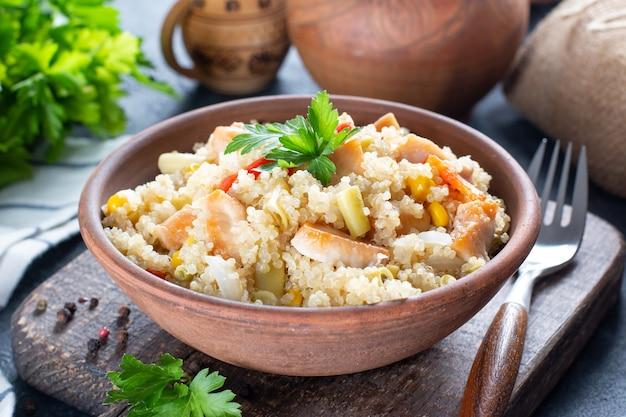 Quinoa-pilaw mit hühnchen und gemüse auf holztisch, selektiver fokus
