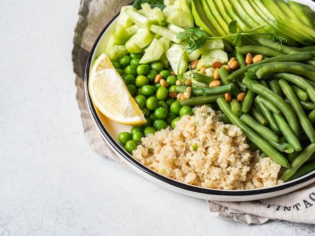 Quinoa-schüssel mit grünen bohnen, grünen erbsen, gurken, avocado und pinienkernen