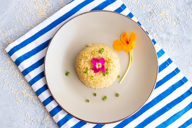 Quinoa-tellerpräsentation verziert mit essbaren blumen