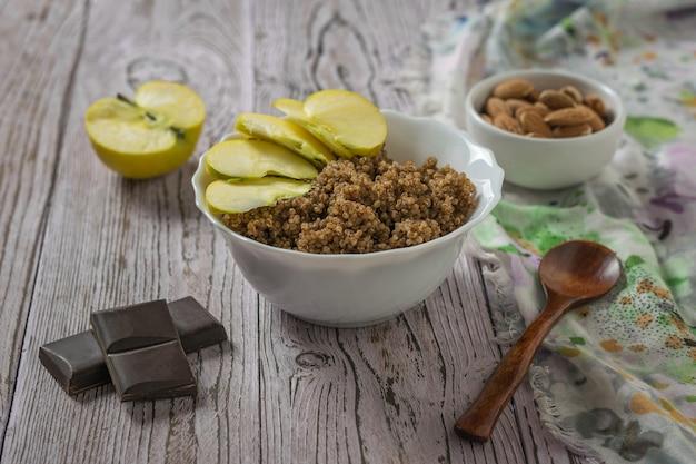 Quinoa und kakaobrei mit apfel auf dem tisch mit stoff. gesunde ernährung.