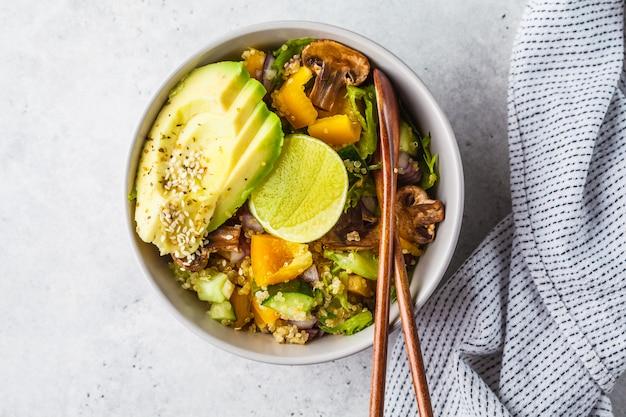 Quinoasalat mit pilzen, gemüse und avocados in der grauen schüssel. gesundes veganes lebensmittelkonzept.