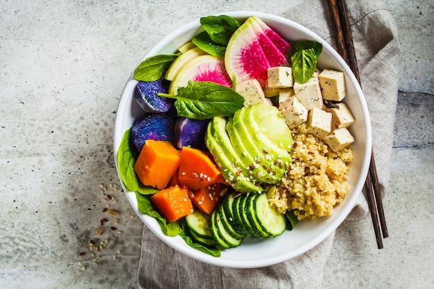 Quinoasalat mit tofu, avocado und gemüse in der weißen schüssel