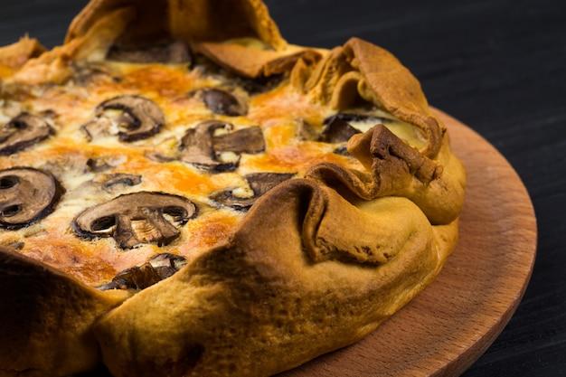Quishe mit pilzen auf einer hölzernen platte