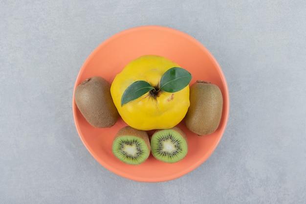 Quitte und geschnittene kiwis auf orangenplatte