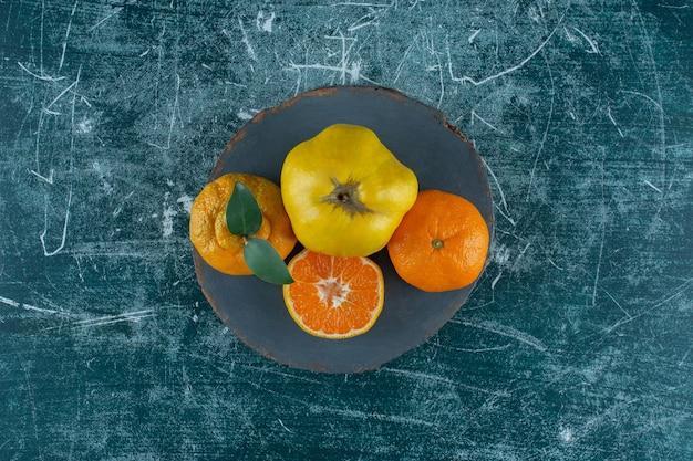 Quitte und orangen auf einem brett, auf dem marmorhintergrund. foto in hoher qualität