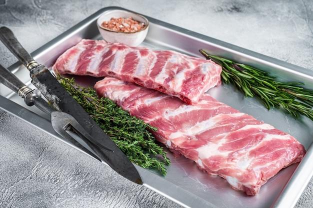 Rack mit rohen schweinerippchen in der küche backblech mit kräutern. weißer hintergrund. draufsicht.