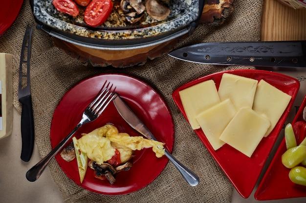 Raclettekäse geschmolzen mit kartoffeln und fleisch. ansicht von oben.