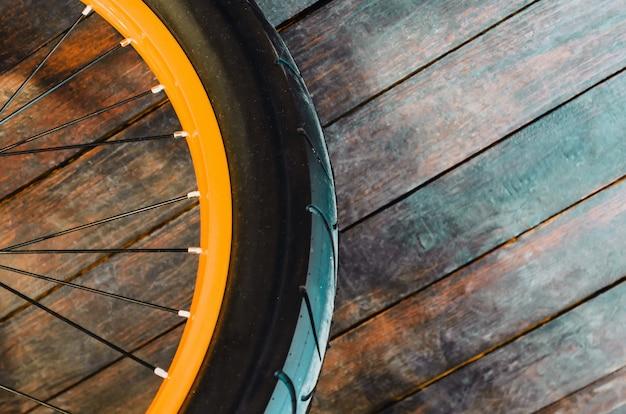 Rad eines stilvollen fahrrads mit einer orange felge und gummireifenabdeckung, hölzernem hintergrund.