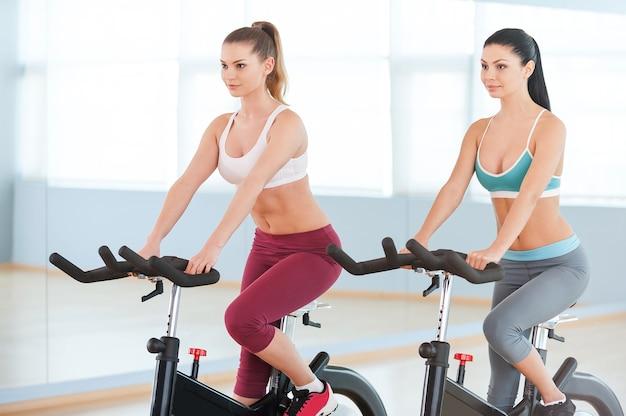 Radfahren auf heimtrainern. zwei attraktive junge frauen in sportkleidung, die auf fitnessfahrrädern trainieren