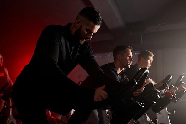 Radfahren mit konzentration. junge kaukasische männer mit perfekten körpern in sportbekleidung radfahren im fitnessstudio