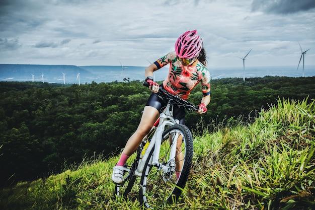 Radfahrenfrau, die auf mountainbike auf die oberseite des berges reitet