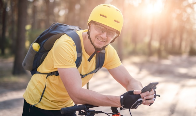 Radfahrer auf dem fahrrad, das gps-navigator im smartphone im kiefernholz überprüft