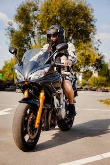 Radfahrer auf dem motorrad, das wartet, um die straße zu kreuzen