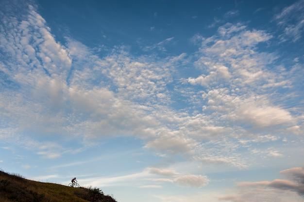 Radfahrer auf einem hügel gegen bewölkten blauen himmel.