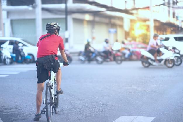 Radfahrer auf fahrrad mit sturzhelmwartekreuzung im gesunden konzept der zyklischen übung mit kopienraum