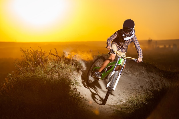 Radfahrer, der abwärts auf mountainbike auf dem hügel fährt