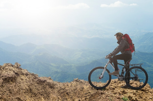 Radfahrer, der auf fahrrad im gebirgsradfahrer auf die oberseite eines hügels fährt