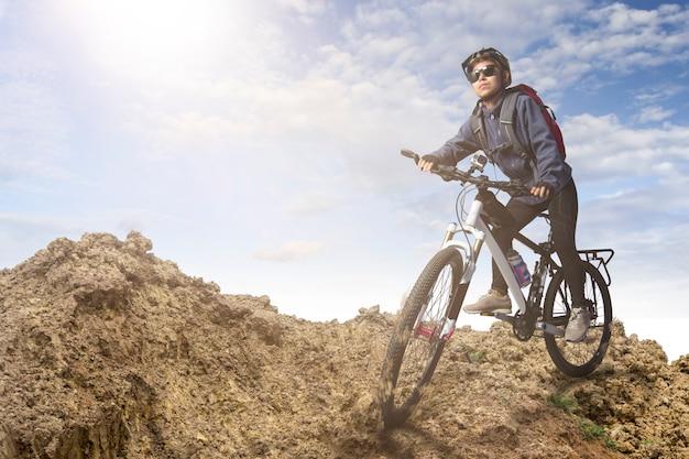 Radfahrer, der auf fahrrad in den bergen auf sonnenuntergang fährt