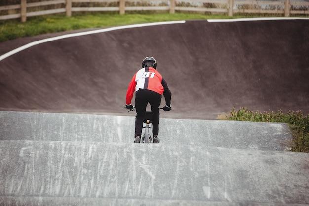 Radfahrer, der bmx-fahrrad im skatepark fährt