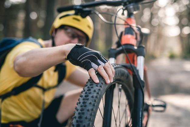 Radfahrer, der den reifendruck des fahrrads vor der fahrt im wald überprüft