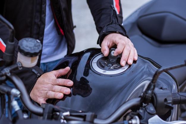 Radfahrer, der den tankdeckel von seinem motorrad entfernt.