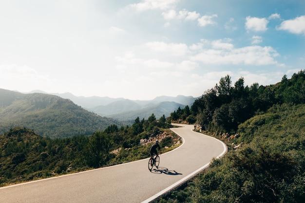 Radfahrer, der ein fahrrad bei sonnenuntergang in einem bergstraßenboden reitet