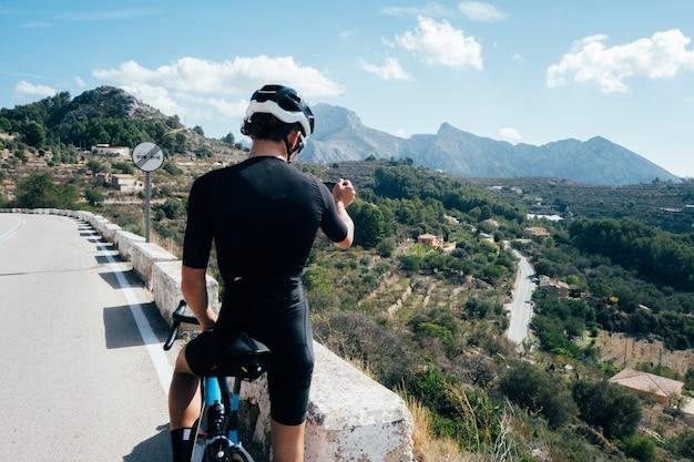Radfahrer, der ein fahrrad bei sonnenuntergang in einer bergstraße reitet