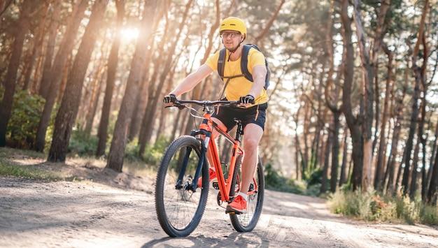Radfahrer, der fahrrad entlang der grundstraße im sonnigen wald fährt