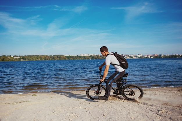Radfahrer, der fahrrad im strand fährt