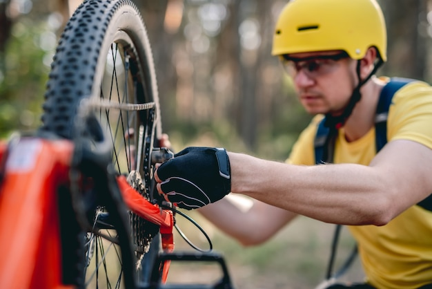 Radfahrer, der im wald einen kettenraddefekt an einem umgedrehten fahrrad überprüft. . . . . . . . . . . . . . . . . . . . . . . . . .
