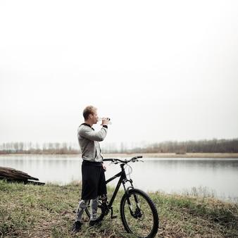 Radfahrer, der mit dem fahrrad betrachtet see beim trinken von wasser von der flasche steht