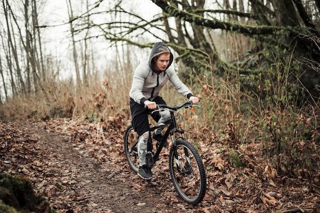 Radfahrer, der mit kapuze spitzenfahrreiten im wald trägt