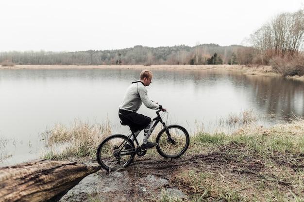 Radfahrer, der seine mountainbike nahe dem idyllischen see reitet