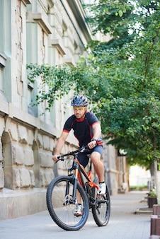 Radfahrer des athletischen mannes, der extremsportarten auf dem fahrrad in den straßen der alten stadt tut.