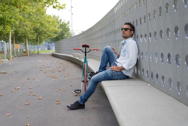 Radfahrer des jungen mannes, der auf einer bank während hörende musik sich entspannt