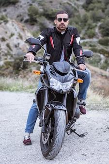 Radfahrer des jungen mannes mit seinem schwarzen motorrad bereit zu fahren
