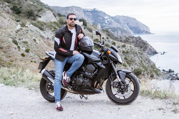 Radfahrer des jungen mannes mit seinem schwarzen motorrad fahrbereit, vor dem meer