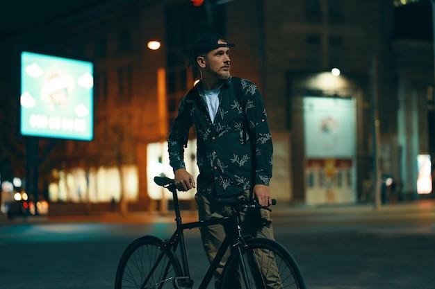 Radfahrer, die neben seinem klassischen fahrrad auf der straße stehen, während sie die nachtstadt beobachten