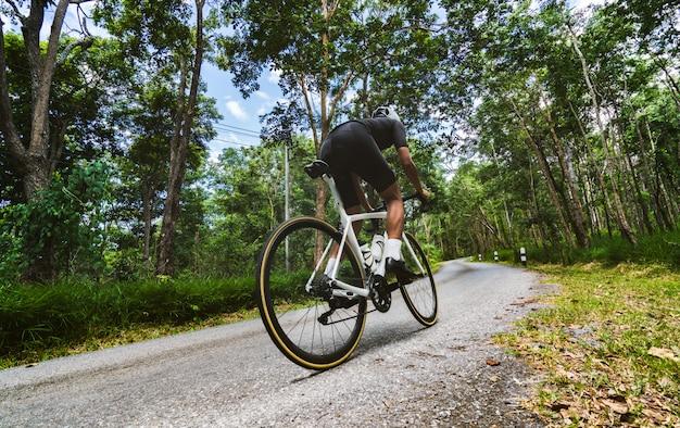 Radfahrer er radelte bergauf im wald.