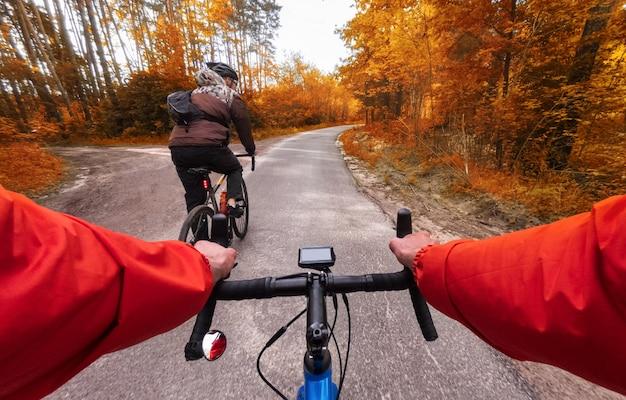 Radfahrer fahren mit dem fahrrad im herbstwald die straße entlang. pov. herbstradfahren im wald.