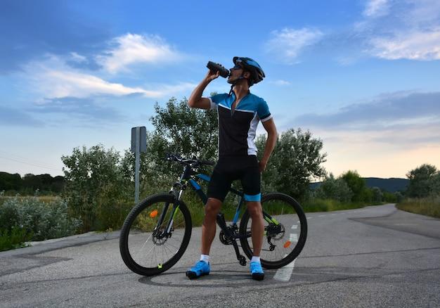 Radfahrer geht mountainbike entlang einer einsamen straße