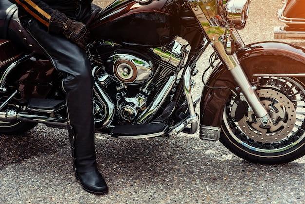 Radfahrer in den schwarzen stiefeln, die auf einem motorrad sitzen