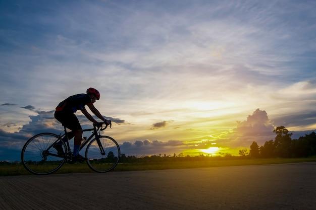 Radfahrer in der bewegung auf schönem sonnenuntergang des hintergrundes mit schattenbild radfahrer im sommerkonzept