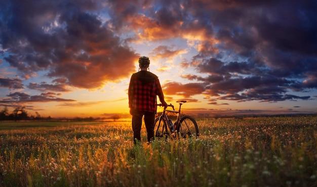 Radfahrer in einem feld, das den dramatischen himmel mit wolken bei sonnenuntergang nach fahrt genießt.