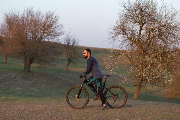Radfahrer in shorts und trikot auf einem carbonrad mit luftfedergabel auf einer klippe stehend