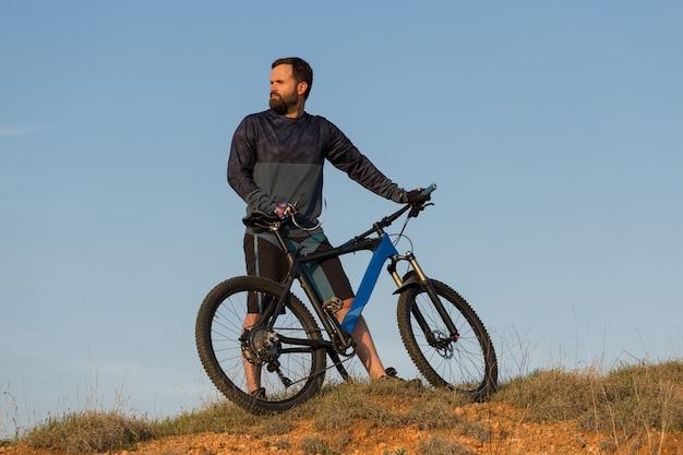 Radfahrer in shorts und trikot auf einem modernen carbon-hardtail-bike mit luftfedergabel