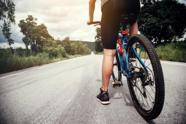 Radfahrer-mann, der das fahrrad im freien läuft