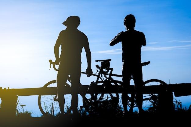 Radfahrer mit einer fahrradschattenbild auf sonnenunterganghimmelhintergrund