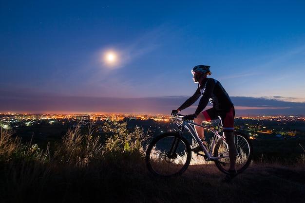 Radfahrer mit mountainbike oben auf dem hügel