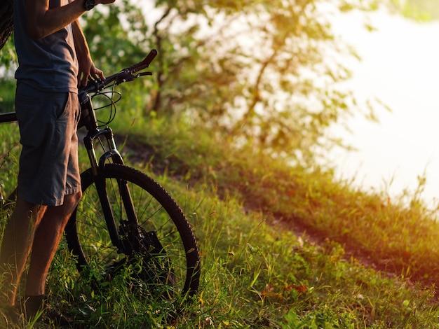 Radfahrer nahe bei dem fahrrad im grünen sommerwald bei sonnenuntergangnahaufnahme